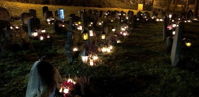 Bild över en kyrkogård kvällstid. Det lyser i lyktor vid varje sten