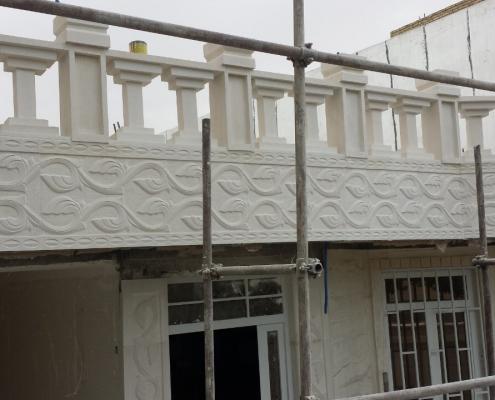 Närbild på balkongräcke med pelare och uthuggna mönster
