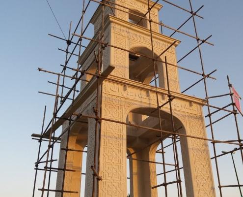 Bild på en stenbyggnad i tre våningar där både basen och valvväggarna har olika mönster inhuggna.
