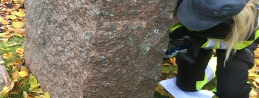 Kvinna med mätinstrument som kontrollerar gravstenen