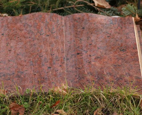 Gravsten i granit formad som en uppslagen bok